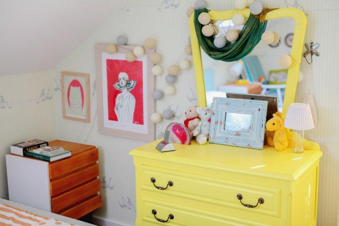Jemné pastelové odtiene v spálni dopĺňa žltý toaletný stolík. Susedí s  nočným stolíkom od retro-design. Nad zrkadlom pózuje