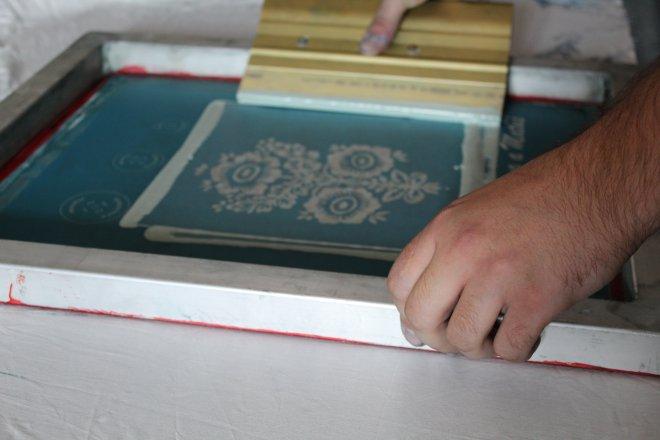 Nanášanie rezervy na plátno technikou sieťotlače v dielni Mateja Rabadu