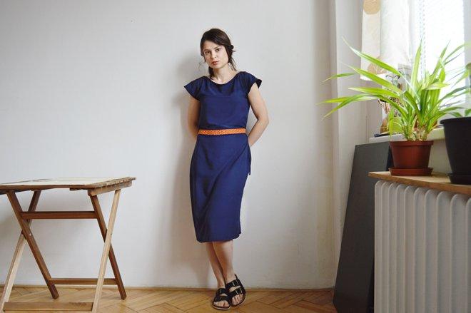 Modré šaty po kolená s lodičkovým výstrihom, krátkym rukávom a oranžovým pásikom.