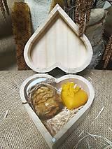 Orechy v agátovom mede a vosková sviečka v tvare srdca na drevenej slame v drevenom srdci