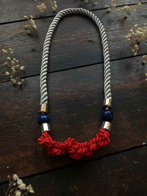 Červené uzlíky na šedém laně